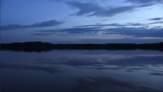 Using video shot in Finland, Campanale lays an ambient track of digital pops and clicks against a perfect, languid, 360 degree pan of a line of trees reflected in a lake at dusk.