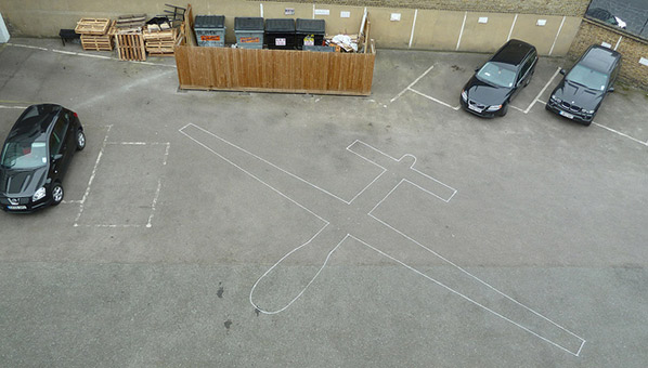 Drone Shadows, image of a car park with the drawing of a drone on the ground