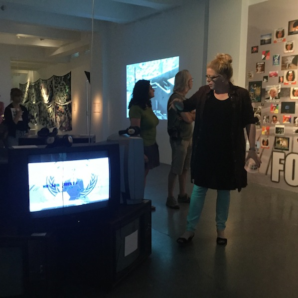 Inke Arns giving a tour of the exhibition. Anonymous (left), Metahaven (far left), Wikileaks' Collateral Murder (middle),  Lulz (right)