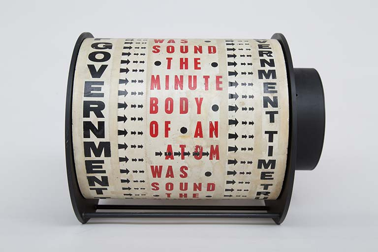 Liliane Lijn. Get Rid of Government Time. 1962. 29.5 x 38 x 30 cm. Letraset on painted metal drum, plastic, painted metal, motor. Words from a poem by Nazli Nour. Frame altered in 1965. Link Here - https://bit.ly/2KcsLpu