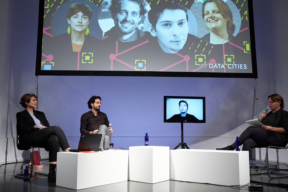 """Panel discussion """"Citizens for Digital Sovereignty: Shaping Inclusive & Resilient Cities"""" with Elizabeth Calderón Lüning (left), Rafael Heiber, Alexandre Monnin (screen), and Lieke Ploeger."""